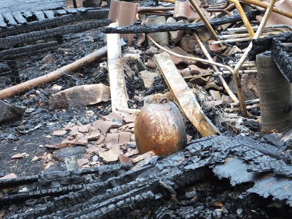 Vår trebenta kittel återfann vi i brandresterna. Den skall nu borstas ren och hammarlackas i svart så att den återigen får pryda sin plats fylld med blommor.