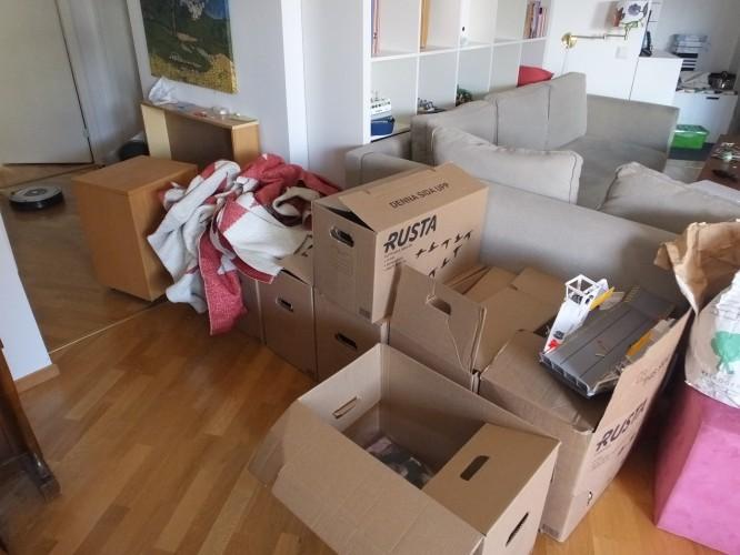 Kartonger med leksaker och böcker som barnen vill ha med sig till nya huset som hamnat bakom soffan.