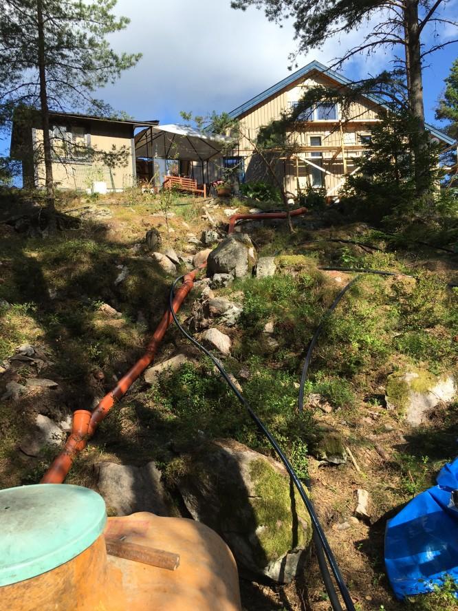 Avloppsdragningen över berget färdigdraget och inkopplat i vår numera frilagda tvåkammarbrunn.