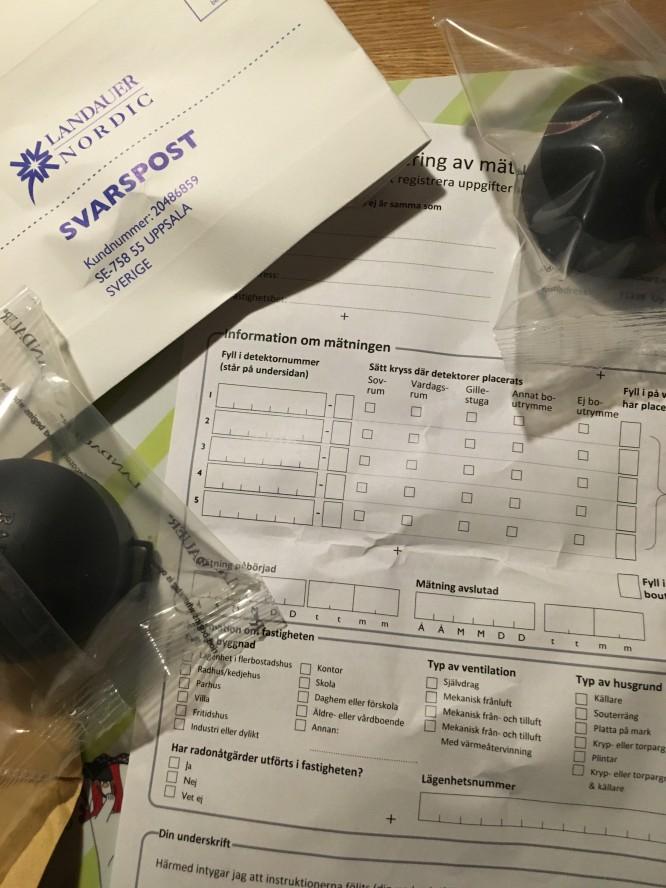 """Innehållet i ett radonmätpaket. Information, formulär, minst två """"radonpuckar"""" och ett svarskuvert."""