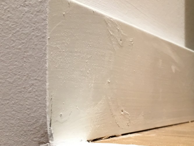 """""""Färdigmålade"""" golvlister med den fabriksmålade grundfärgen och sedan någon tjock vit färg med annat glanstal slarvigt påstruket över spikhålen."""