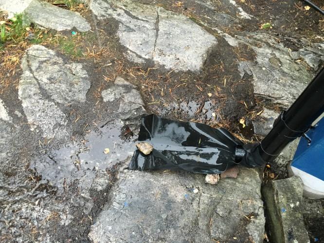 Tillfälligt förbättrad takavrinning med hjälp av gummisnodd, några stenar och gummiduk.
