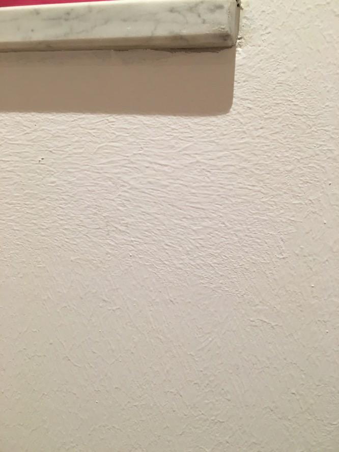 Grovkornigt målat med för tjockt med färg på för grov roller. Dessutom har man målat i olika riktningar så det liknar snarare en strukturtapet än en målad vägg.