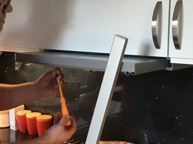 Maken som monterar front till spisfläkt