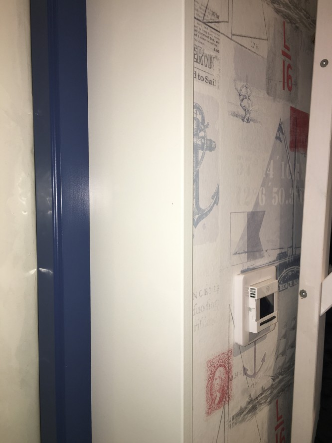 Ytterdörrens blåa karm matchar tapetens blåa färg.