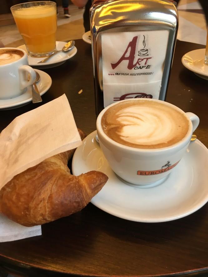 Italiens frukost cappuccino och crossiant.