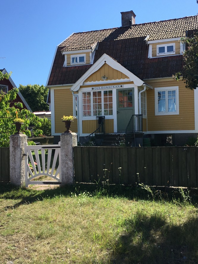 Ett vackert putsat gult hus bland alla faluröda små trähus.